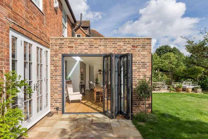 A casa de tijolinhos acertou em cheio com o uso da porta sanfonada de ferro e vidro