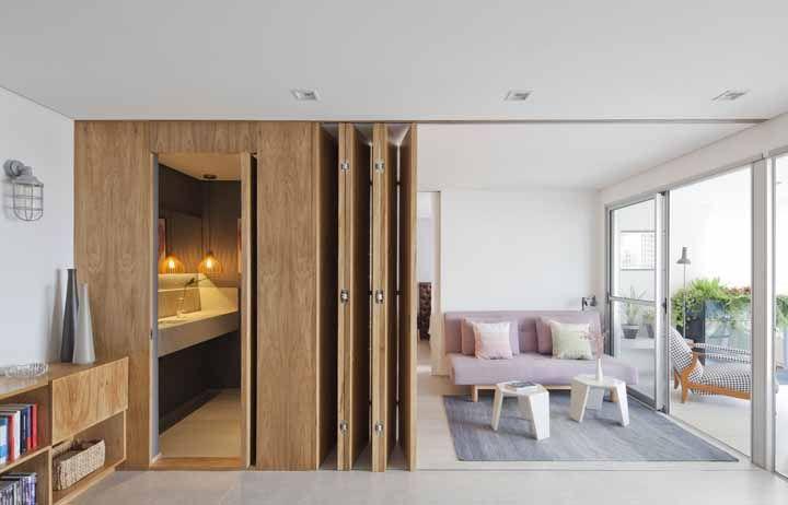 A mesma madeira que reveste a parede foi usada para criar a porta sanfonada