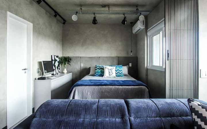 O quarto de casal de estilo industrial apostou em uma porta sanfonada de ferro