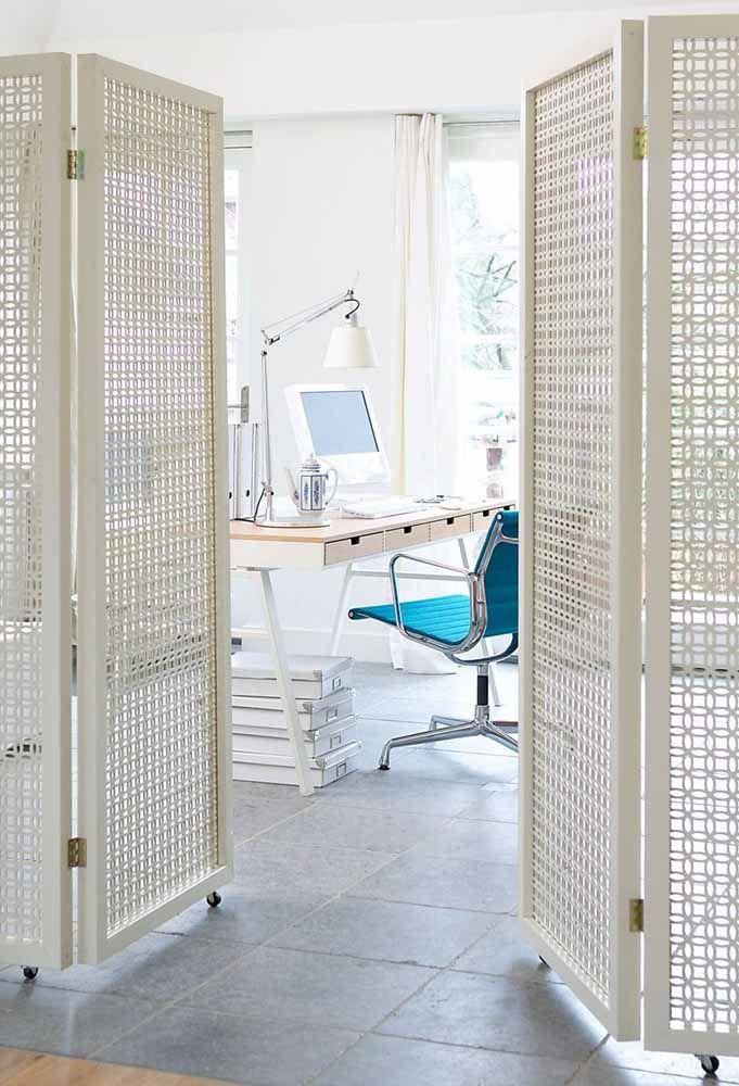 Aqui, a porta sanfonada branca de madeira tem a função de isolar o escritório dos demais ambientes