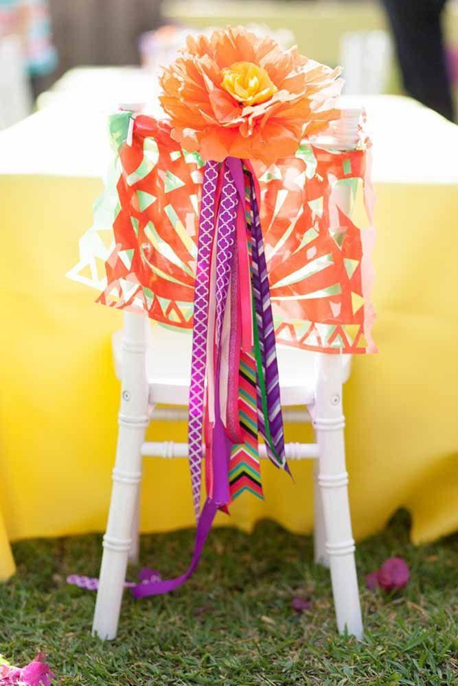 Decore as cadeiras da festa com flores gigantes de papel crepom