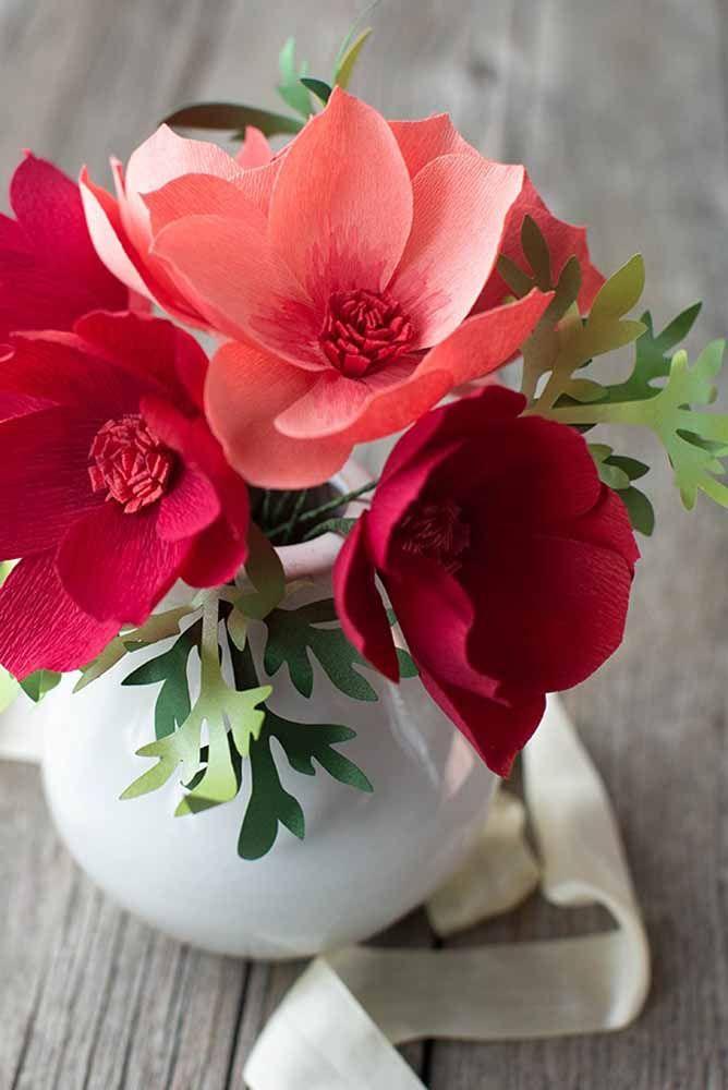 O vaso branco de cerâmica ajuda a destacar as flores de papel em tons quentes e vibrantes