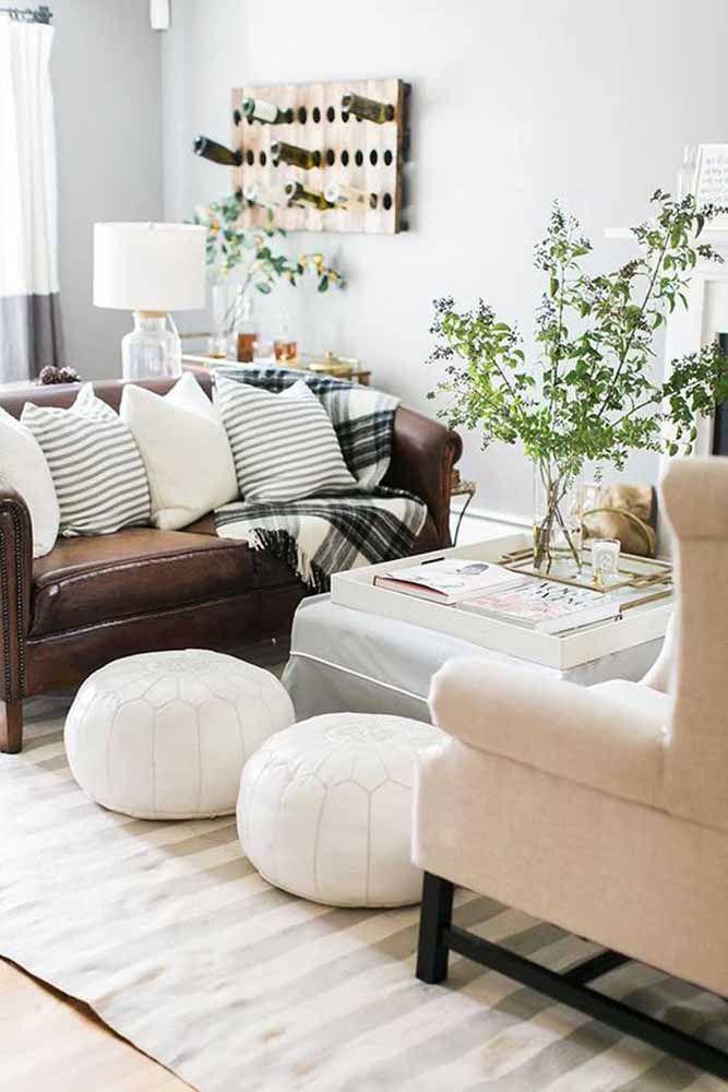 Sofá de couro marrom combinado às almofadas branca e preta: união entre tons e materiais clássicos e que nunca saem de moda