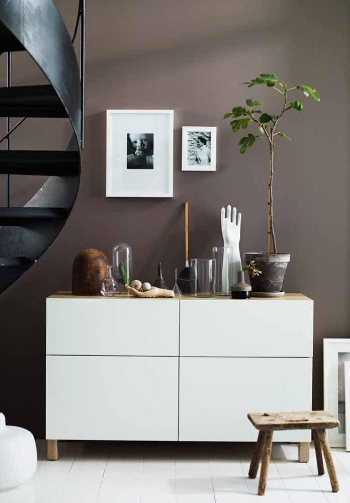 Quase cinza: esse tom de marrom na parede traz seriedade ao ambiente; repare, contudo, que as peças decorativas quebram essa impressão