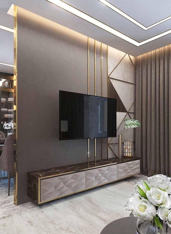 Já aqui nessa sala o mármore marrom do rack se destaca na companhia dos frisos dourados