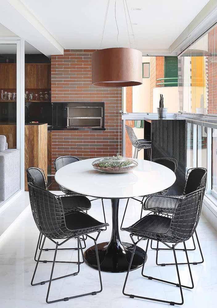 E na varanda gourmet, o marrom aparece de modo marcante na luminária; mas os tijolinhos ao fundo não deixam a cor ficar sozinha no ambiente