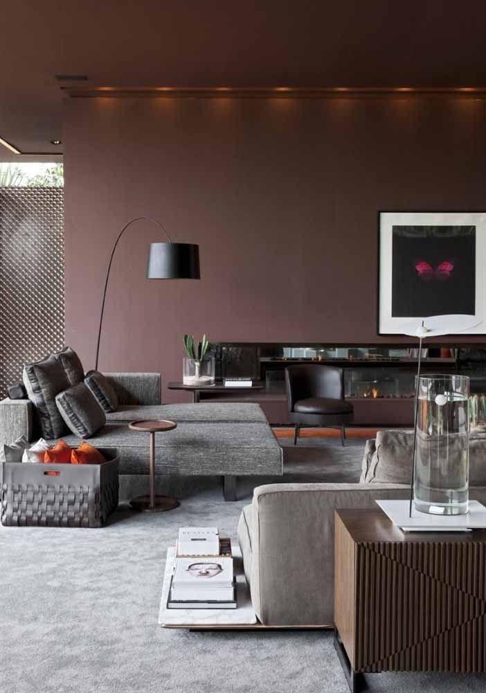 A sala de paredes marrom apostou em uma mobília cinza para reforçar o estilo refinado e clássico da decoração