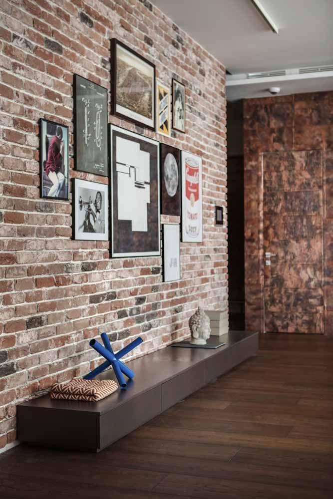 Nesse ambiente o marrom aparece salpicado em diversos pontos: na coloração dos tijolinhos, nos quadros, na parede de pedra ao fundo, no rack e no piso