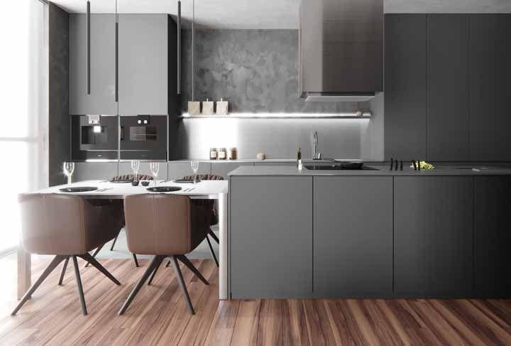 A cozinha cinza fica mais agradável visualmente com a presença das poltronas marrons