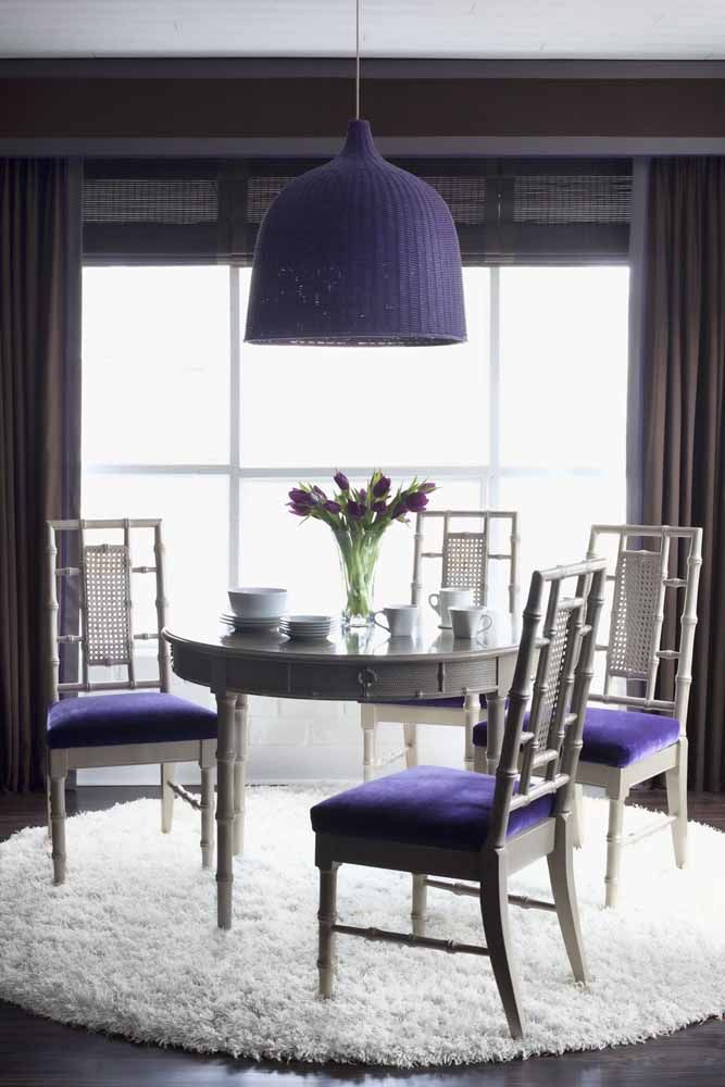 Ambiente clássico, mas com um toque roxo de ousadia nas cadeiras, luminárias e nas tulipas sobre a mesa