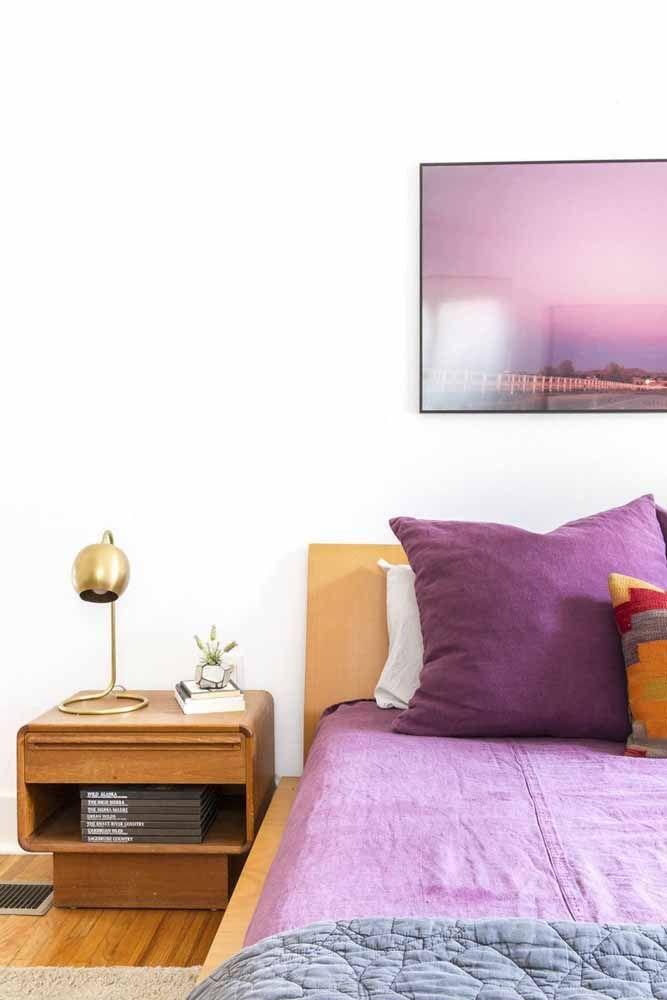 O lençol roxo não ficou sozinho nesse quarto; o quadro na parede completa a composição de tons