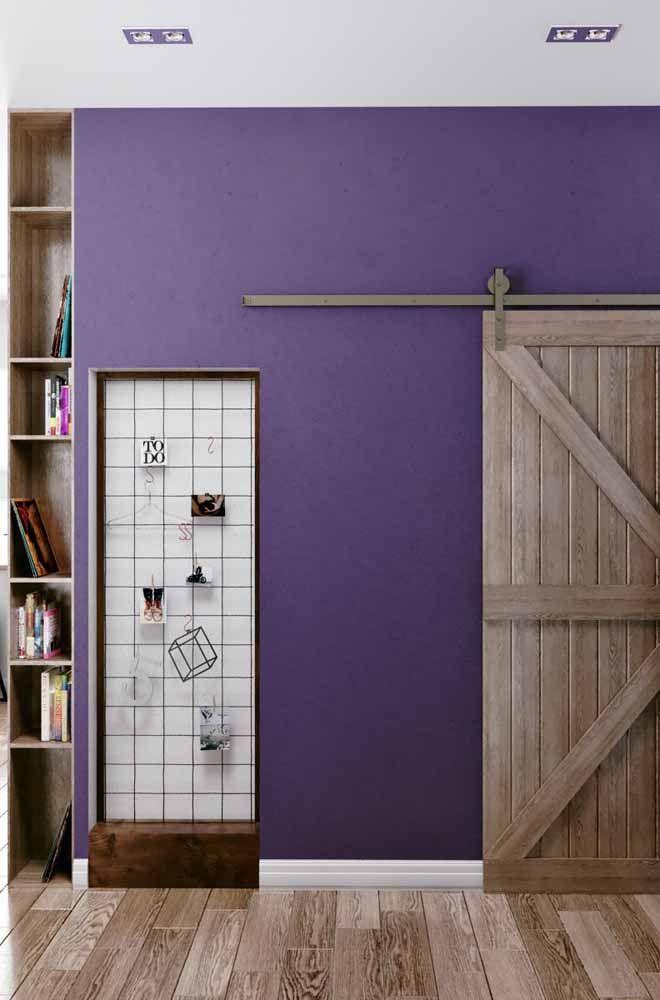 A parede roxa combinada aos elementos em madeira deixou o ambiente confortável e acolhedor