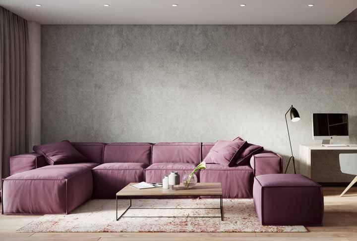 Para o sofá roxo ser o centro das atenções, a opção foi deixar a parede cinza