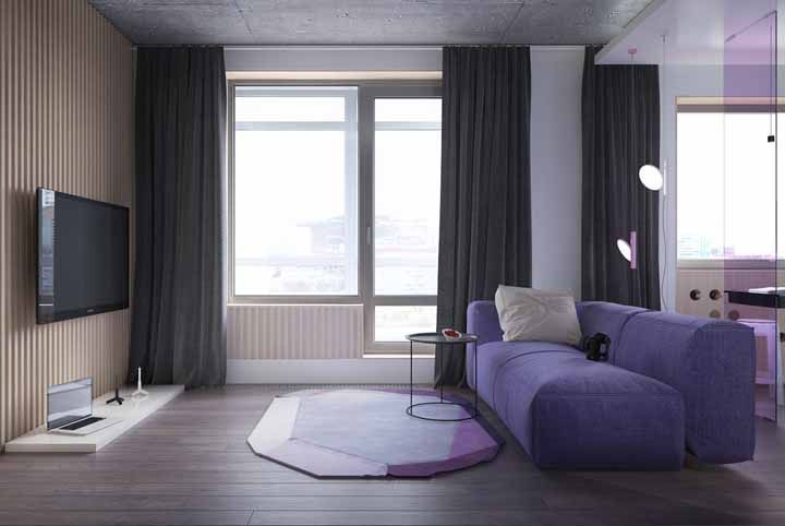 As formas geométricas do tapete ganharam tonalidades diferentes de roxo; para completar o cenário o sofá azul