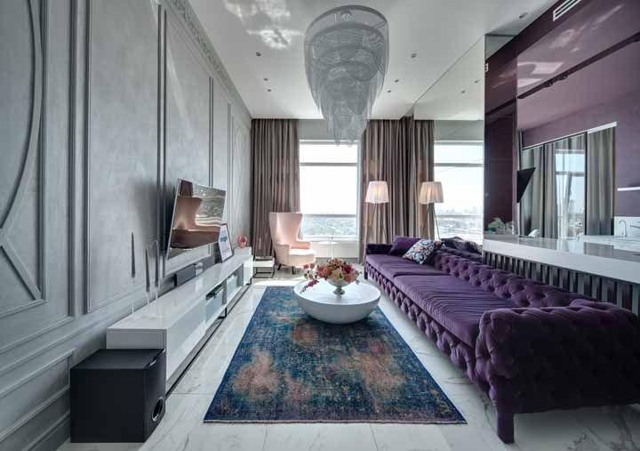 A máxima expressão do luxo e da sofisticação: sofá de veludo roxo com acabamento capitone; o lustre e a parede com boisserie completam a proposta