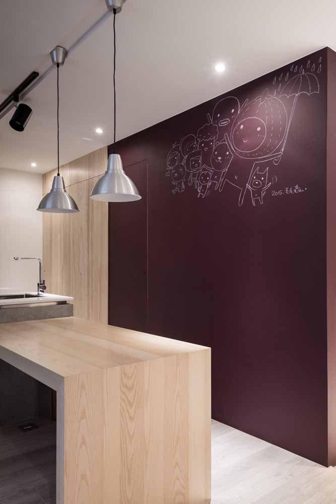 O roxo avermelhado foi usado na parede dessa cozinha em combinação com o tom amadeirado