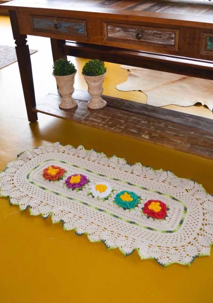 Flores coloridas formando o centro deste tapete oval branco em crochê
