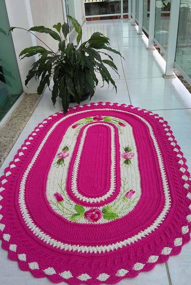O pink para a estrutura e o detalhe das flores neste outro exemplo de tapete para entradas