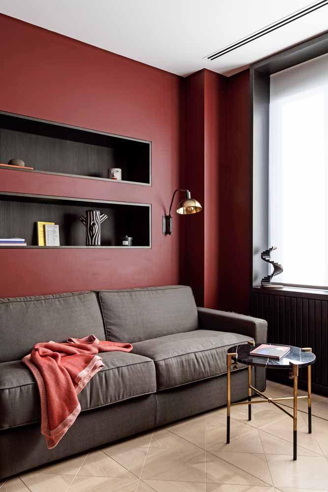 O vermelho queimado foi usado nessa sala em combinação com o cinza: a mistura conferiu sobriedade e aconchego na medida certa