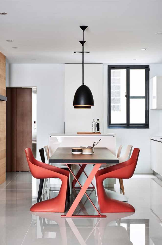 Curvas sinuosas e um vermelho intenso: bastaram duas cadeiras com essas características para radicalizar a cara da cozinha