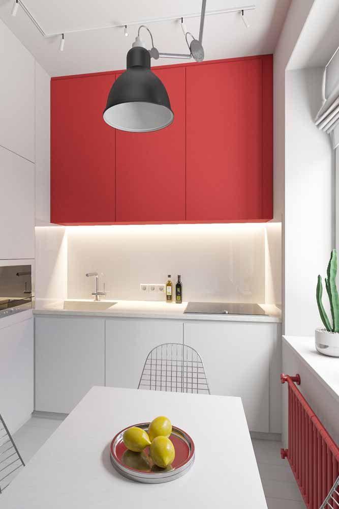 Para quebrar a brancura da cozinha, uma parte do armário foi produzida em vermelho
