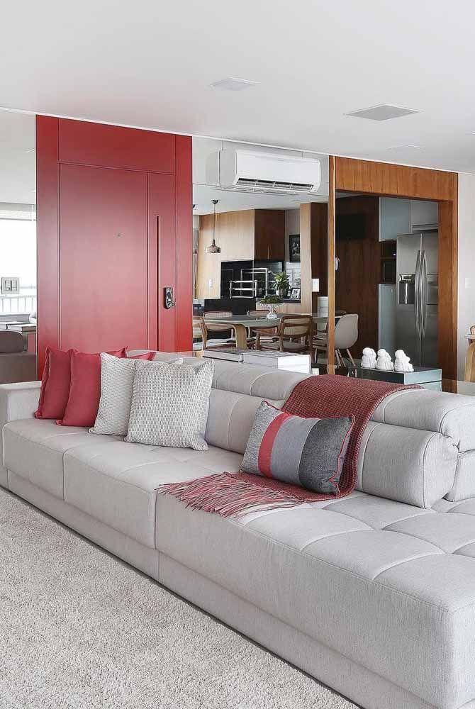 Capas de almofada com estampas em vermelho: quando cansar é só trocar; já a porta vermelha permanece no local dando aquele toque de refinamento à sala