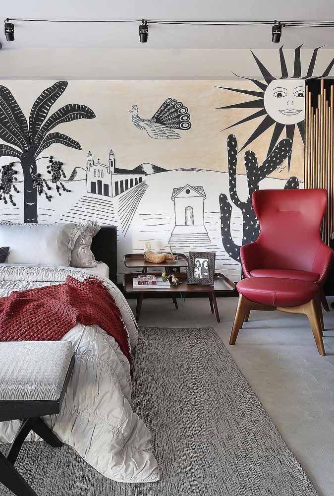 A poltrona vermelha destaca o cordel pintado na parede; para completar a manta na mesma cor sobre a cama