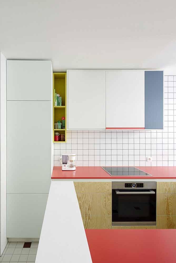 Cozinha de base branca investiu no uso das cores primárias, especialmente o vermelho