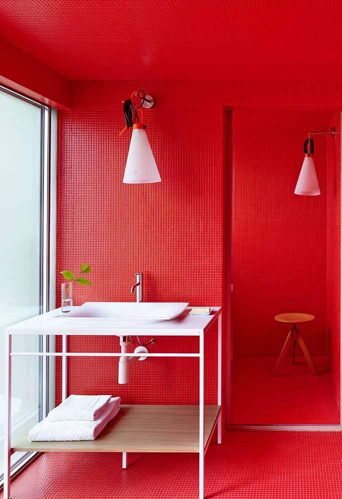 No banheiro todo vermelho, os acessórios brancos se destacam