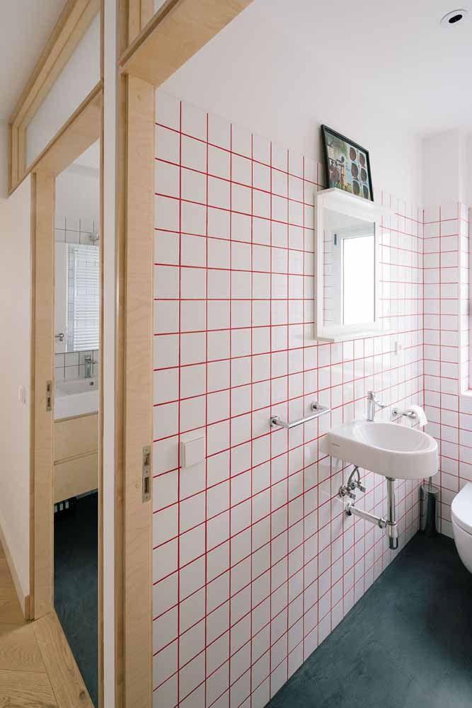 Nesse banheiro, o vermelho aparece no rejunte entre os azulejos brancos