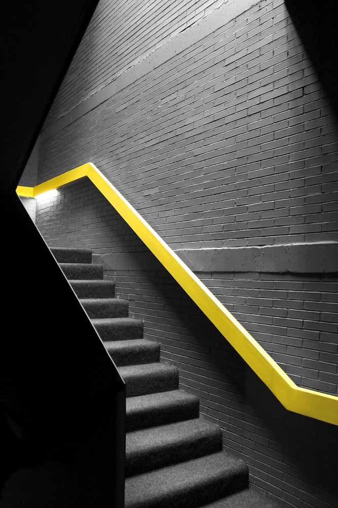 Para realçar a parede cinza de tijolinhos, um corrimão amarelo vivo instalado diretamente na parede