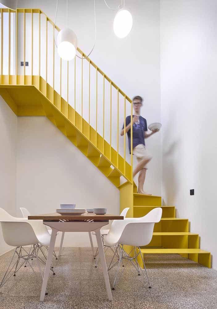 A escada e o corrimão amarelo de ferro são os grandes destaques desse ambiente