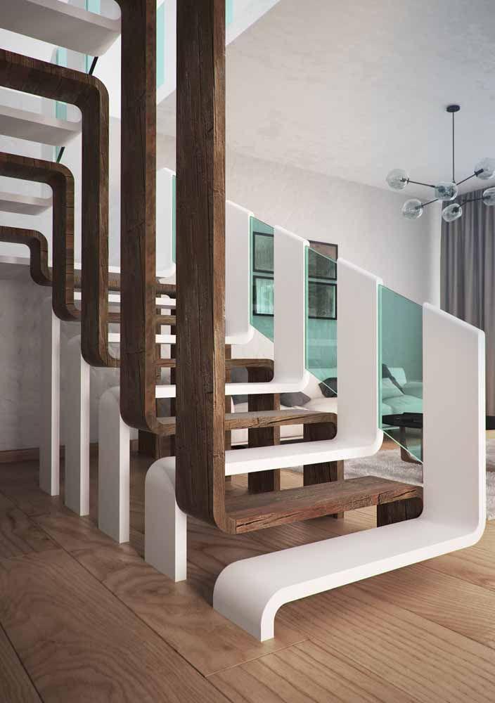 Escada preta contornada por um corrimão dourado; destaque também para o formato diferenciado da peça