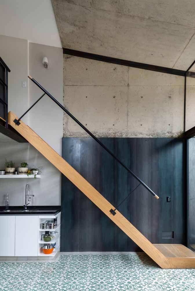 A pequena escada de madeira que dá acesso ao mezanino ganhou um corrimão discreto de metal; contudo esse modelo não é indicado para casas com crianças – por causa do vazado - e idosos – pois não abrange todo o trajeto