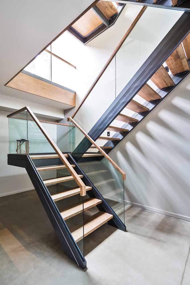 A escada em U faz uma combinação interessante de materiais, entre eles o vidro e a madeira usados no corrimão
