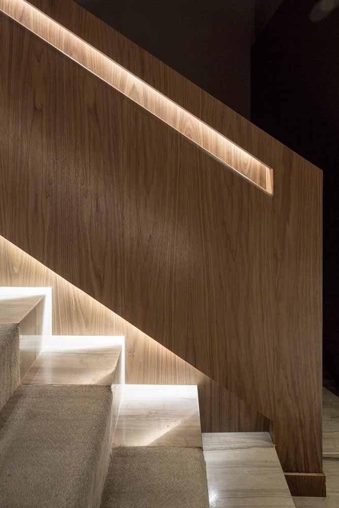 Corrimão todo fechado de madeira com abertura apenas nas áreas que receberam iluminação