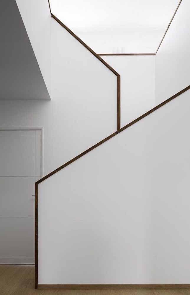 Corrimão de madeira contorna toda a escada que fica escondida pelo guarda corpo de concreto