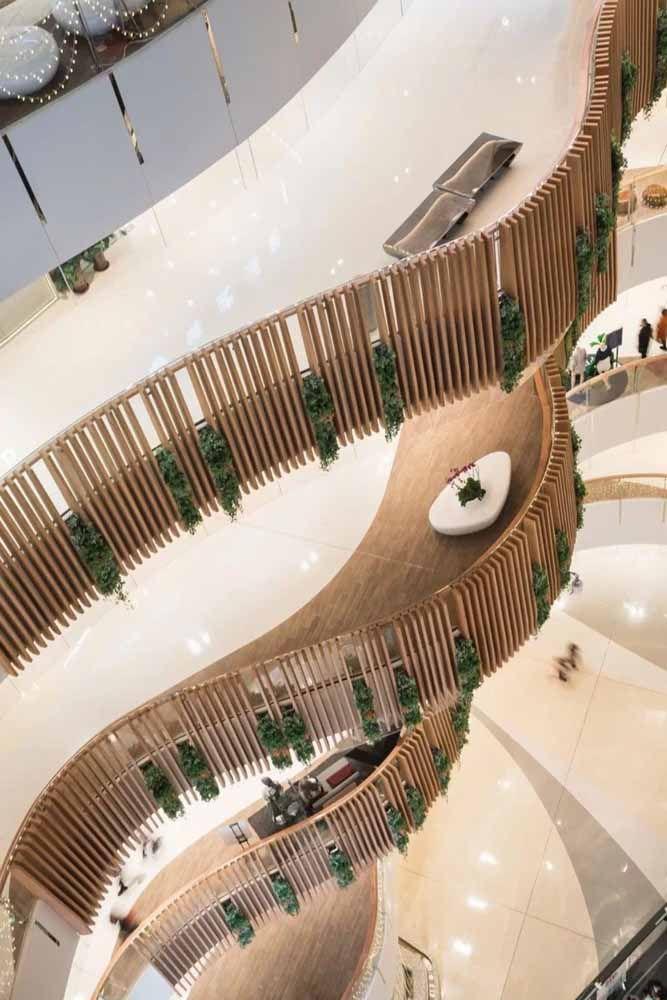O corrimão de linhas verticais de madeira acompanha o formato sinuoso da construção e traz ainda algumas plantas suspensas, lembrando um mini jardim vertical