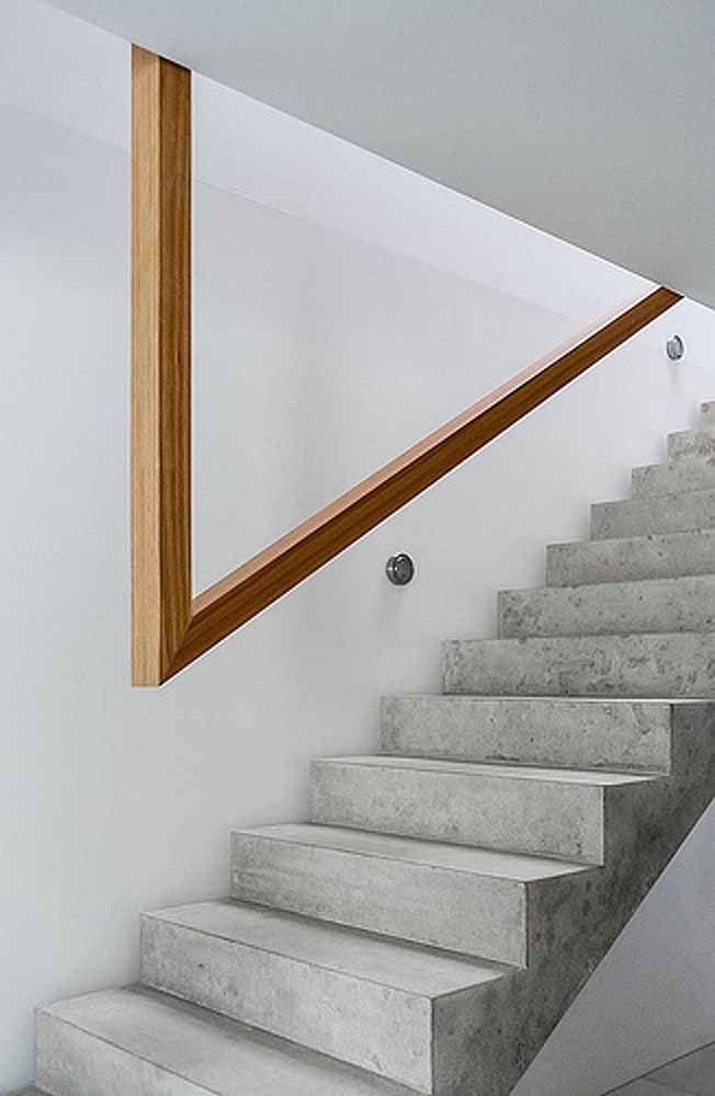 Contraste de materiais: a escada de cimento queimado ganhou um corrimão suspenso de madeira