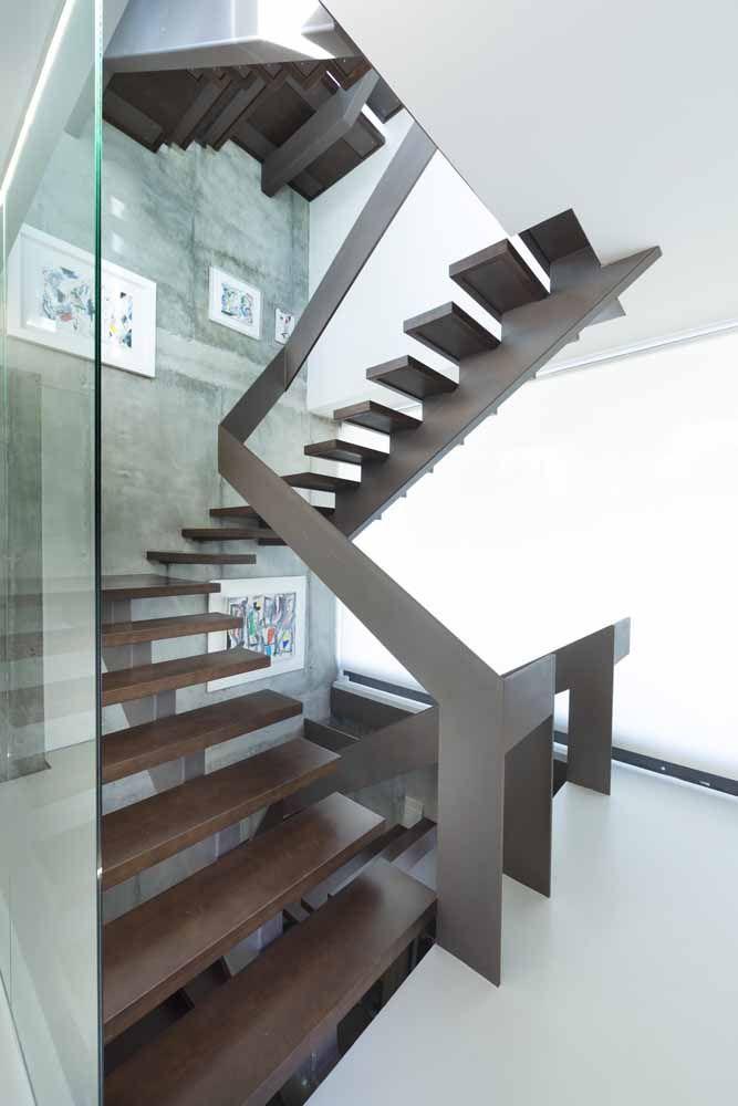 Corrimão de ferro marrom contorna a escada com graça e estilo