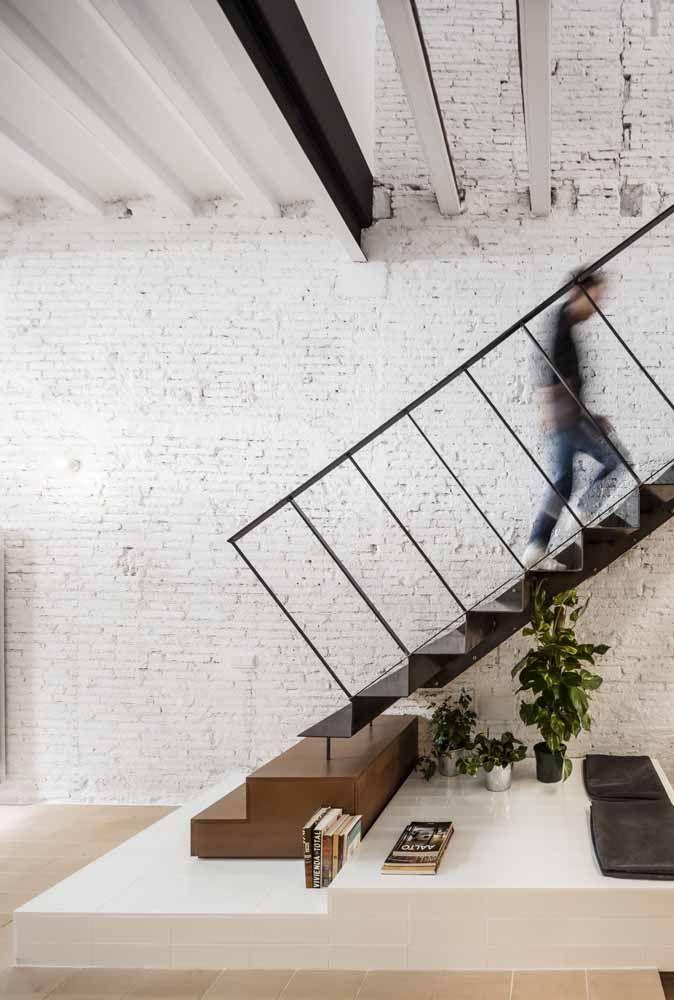 A escada que começa em madeira segue com degraus e corrimão de ferro; um vidro quase imperceptível preenche os vãos e torna a escada mais segura