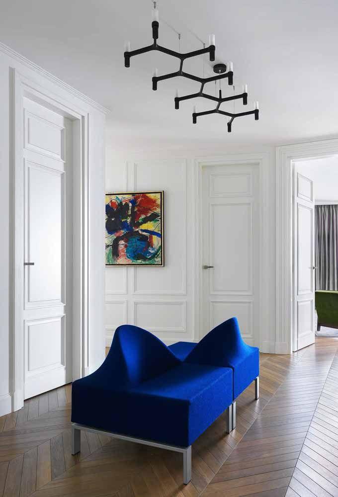 O recamier de design diferenciado e azul intenso é o grande destaque desse ambiente branco e clean
