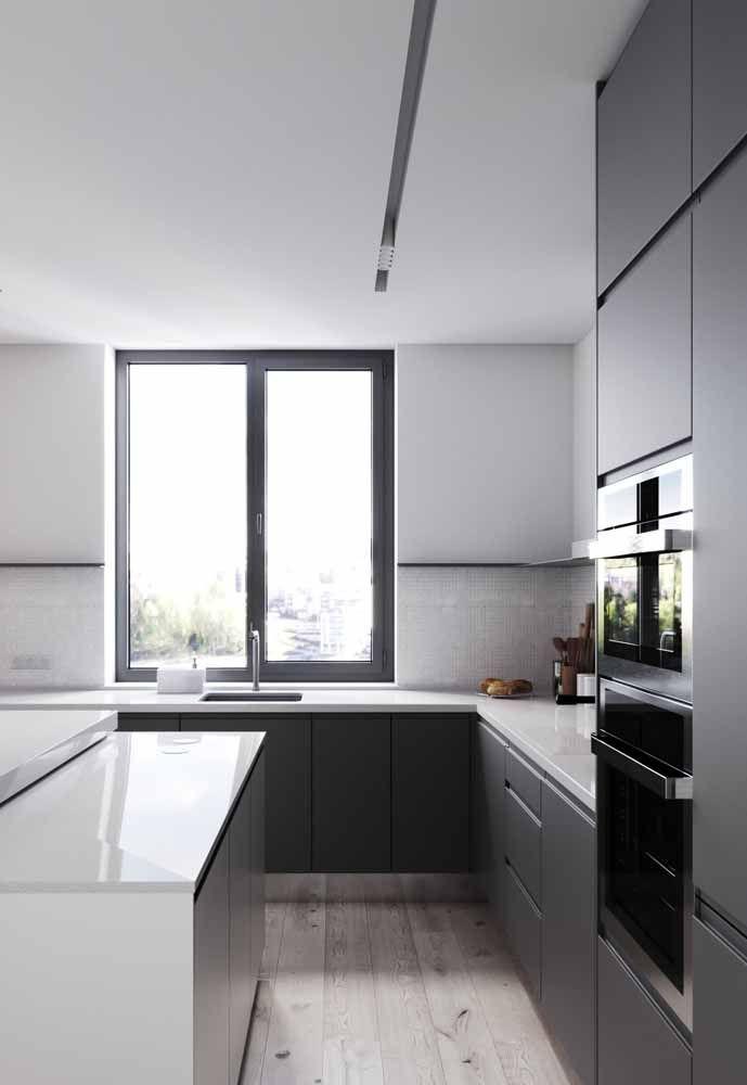 Os armários pretos dessa cozinha não sobrecarregaram o ambiente, graças a alguns fatores como o tamanho do cômodo, a luz natural e as linhas retas do móvel