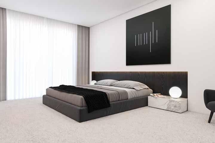 Aqui é o quadro preto que se destaca na parede da cama