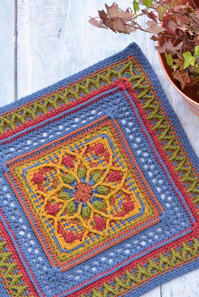 Os tons fechados e escuros foram os escolhidos para esse outro tapete de crochê quadrado com flores