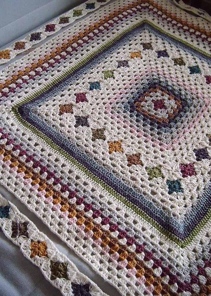 O tom cru do barbante forma um contraste bonito com as cores mais escuras que compõe esse tapete de crochê quadrado