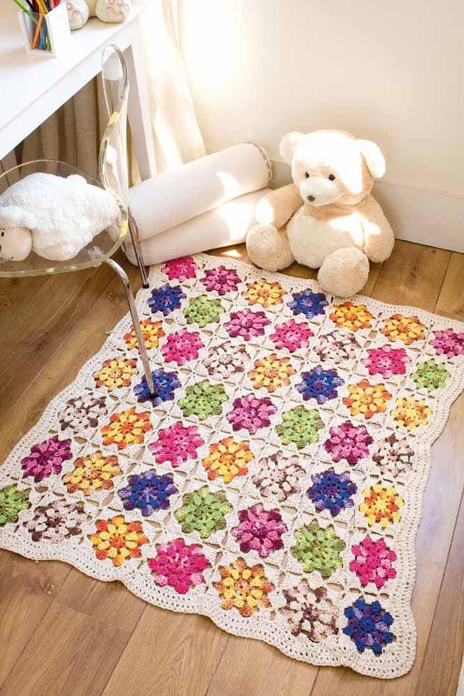 Squares de crochê com flores formam esse lindo e delicado tapetinho para o quarto de bebê
