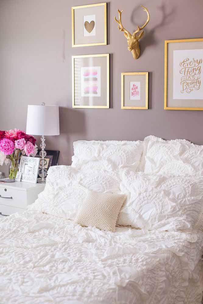 A parede pintada totalmente na cor lilás destaca os itens decorativos que estão em dourado