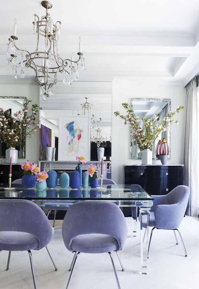 As cadeiras em lilás combinam perfeitamente com a mesa totalmente de vidro