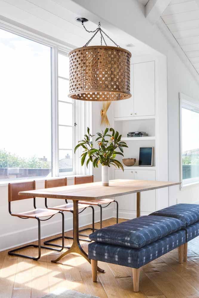 Sofá azul marinho trazendo personalidade para essa sala de jantar em estilo escandinavo, provando que circula bem por diversos estilos.